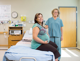 Happy Nurse And Pregnant Woman In Hospital Room