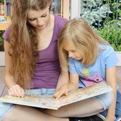 Babysitter schaut Bilder-Buch mit Kind