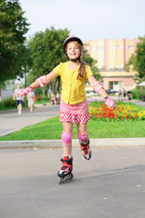 Girl in a helmet, elbow pads and knee pads roller-skating