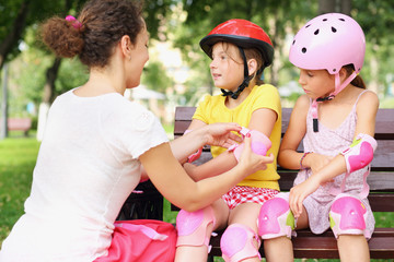 Young woman helping to put on elbow pads two girls