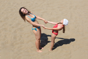 A young woman with a little girl standing on the sand