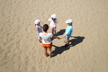 woman with children stand in a circle holding hands