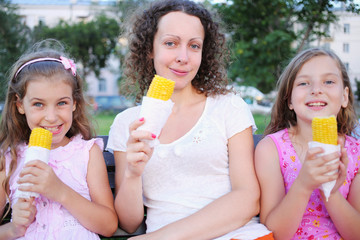 Young woman with two girls eating boiled corn
