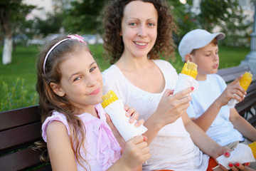 Young woman with two children eating boiled corn