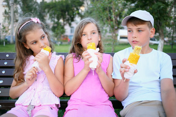 A boy and two girls eating boiled corn