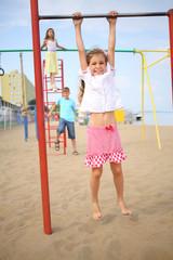 Three children have fun on the playground