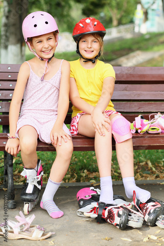 Two girls sitting on the bench and put on rollers