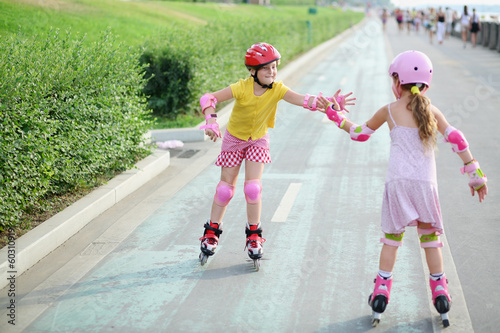 Two girls in roller skates, knee and elbow pads ride on rollers