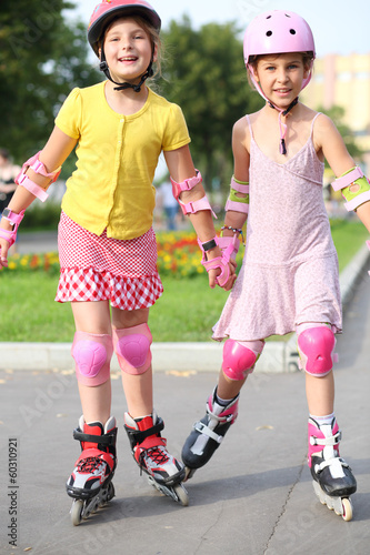 Two girls ride on roller skates in the park