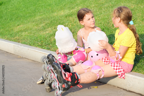 Two girls in roller skates eating candy-floss
