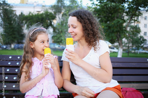 A mother and daughter eating boiled corn