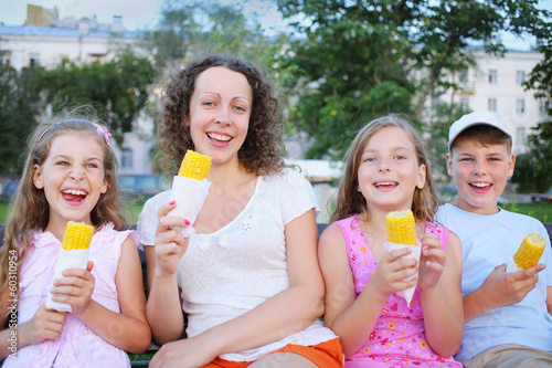Young woman with three children eating boiled corn