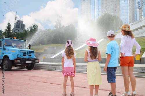 Woman and three children are looking at a car