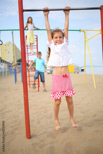 Three children have fun on the playground