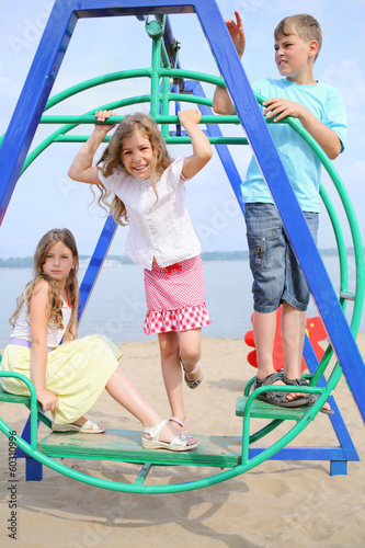 Two girls and a boy on the swing