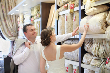 Beautiful newly married couple choose bedding in store