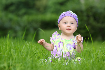 Little girl in a knitted hat sitting on fresh grass