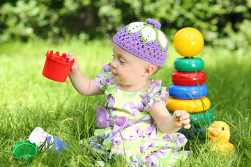 Cute little girl is playing with toys while sitting on the grass