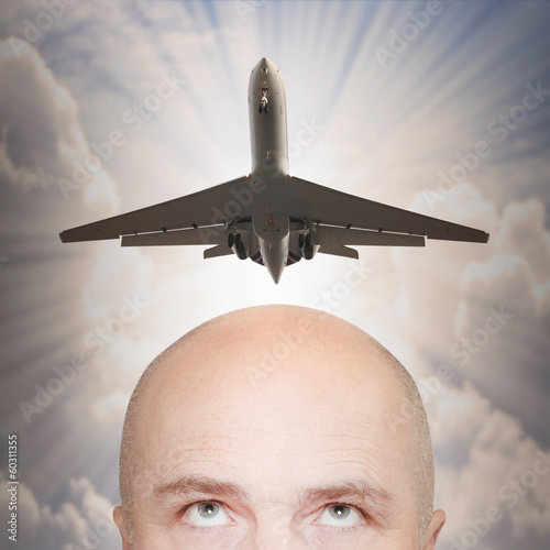 An man and passenger plane over his head. Travel concept.