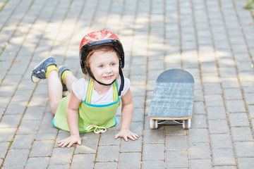 Little girl in protective helmet lies on park path near to skate