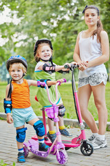 Two little children on scootes and teenage girl in park