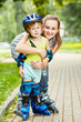 Smiling teen girl and little boy in roller protective equipment