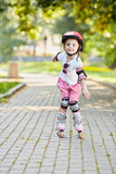 Little girl in protective equipment roller-skates on walkway