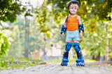 Little boy in protective equipment and rollers stands on walkway