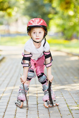 Little girl in protective equipment and rollers stands on park