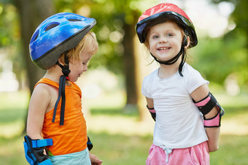 Little boy and girl in roller equipment stand together in summer