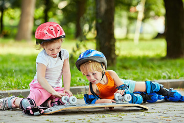 Little boy and girl in roller equipment sit on walkway in summer