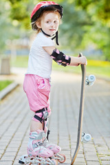 Little girl in protective equipment and rollers stands