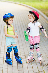 Little boy and girl in roller equipment stand on walkway