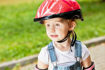 Closeup portrait of little girl in red protective helmet