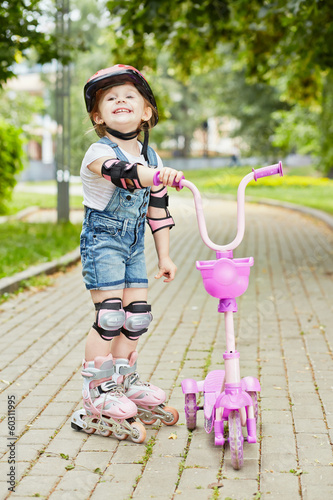 Smiling little girl in roller and protective equipment stands