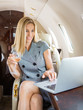 Businesswoman Using Laptop In Private Jet