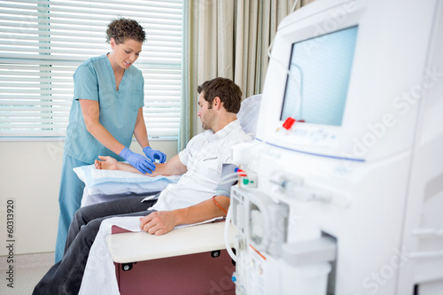 Leinwandbild Motiv Nurse Injecting Patient For Renal Dialysis Treatment