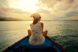 Fototapety Woman traveling by boat at sunset among the islands.