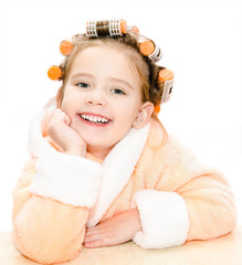 Happy cute little girl in hair curlers and bathrobe isolated on