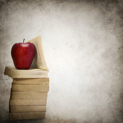 Grunge background with stack of books and red apple