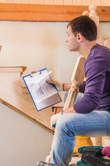 a young carpenter holding blueprint and sitting on ladder