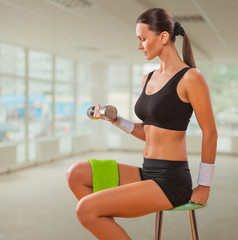beautiful female lifting weight and sitting on chair