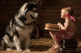 Little girl reading a book to his dog in the barn