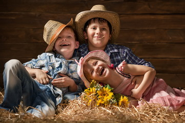 Three laughing children on hay in a hangar