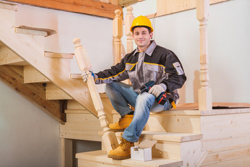 worker sitting on ladder holding wooden post and cordless drill
