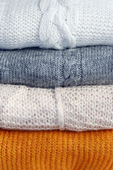 A stack of warm winter knitted sweaters