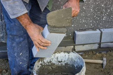 builder holding a brick and with masonry trowel spreading and sh