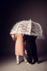 little funny boy and girl sitting under umbrella