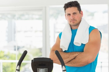 Serious young man working out at spinning class