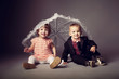 little funny boy and girl sitting under umbrella
